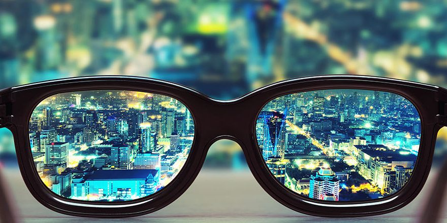Night cityscape focused in glasses lenses. Vision concept